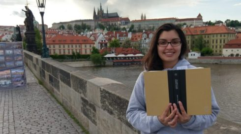 Dhruti in Prague holding up a Book of the Month book