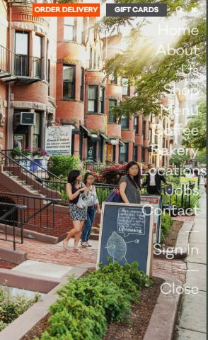 Cafe website with menu overlaid over a photo. The menu is in a transparent white and the photo background is of a sunny street in Boston
